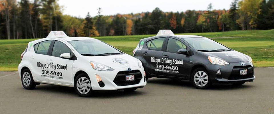 Picture showing 2 hybrid vehicles, one white and one black, with Dieppe Driving School logo and contact information